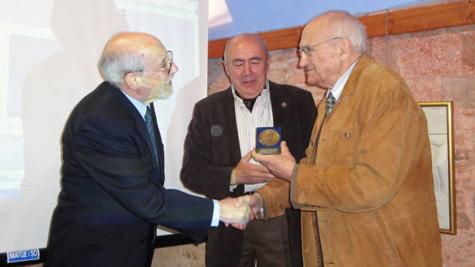 Instant en què el president i el vicepresident de l'Associació Amics del Castell de St. Ferran lliuren la medalla a en Francesc Clarà.
